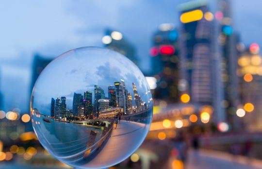 crystal ball with office buildings in-person meetings